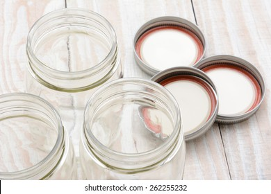 Closeup of three glass canning jars on a rustic wood farmhouse style kitchen table. The lids are laying in the background. Shallow depth of field with focus on the jar rims.