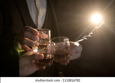 Close-up of three hands of men in suits clink glasses of whiskey drink alcoholic beverage together on a black background with a ray of light. Business concept. Space for text.