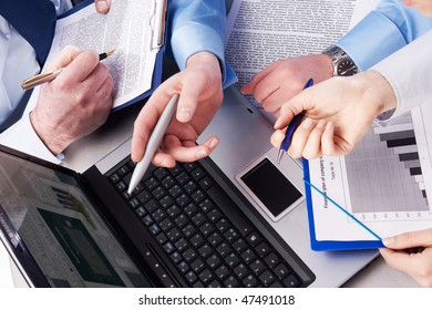 Close-up of three hands pointing at desktop