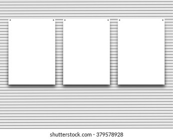 Close-up of three hanged paper sheet frames with nails on grey striped wallpaper background
