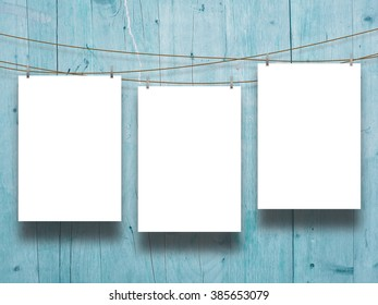 Close-up of three hanged paper sheet frames with pegs on aqua wooden boards background