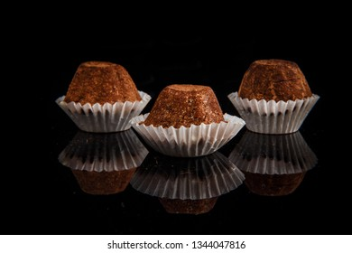 closeup three healthy useful organic handmade round chocolate candies decorated with brown cocao powder on black mirror background