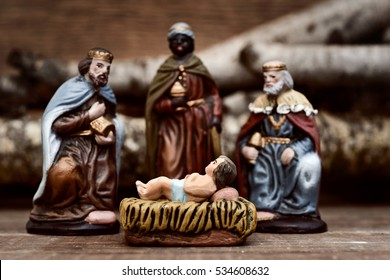 closeup of the three kings carrying their gifts adoring the Child Jesus on a rustic scene
