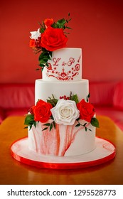 Close-up of three layered wedding cake decorated with red and white edible roses placed indoors on the wooden table