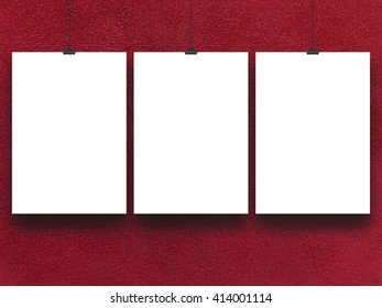 Close-up of three nailed blank frames hanged by clips against red rough plastered wall background