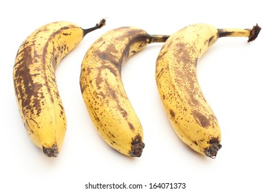 Closeup of three overripe and old bananas isolated on white background