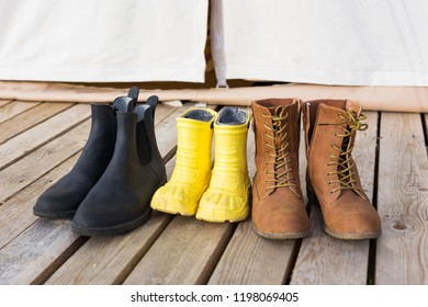 Close-up of three pair of shoes on wooden terrace behind of glamping tent. Family camping concept