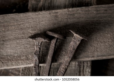 closeup of three rusty nails on a wooden cross, depicting the holy nails and the holy cross