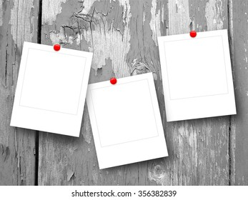 Close-up of three square instant photo frames with pins on weathered wood background