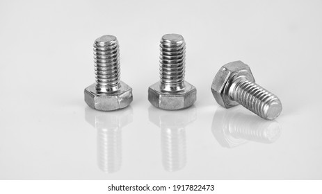 A closeup of three stainless steel bolts isolated on a white background