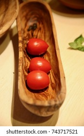 Closeup of three very fresh roma tomatoes in a wood dish