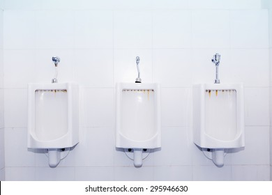 Closeup of three white urinals in men's bathroom, design of white ceramic urinals for men in toilet room