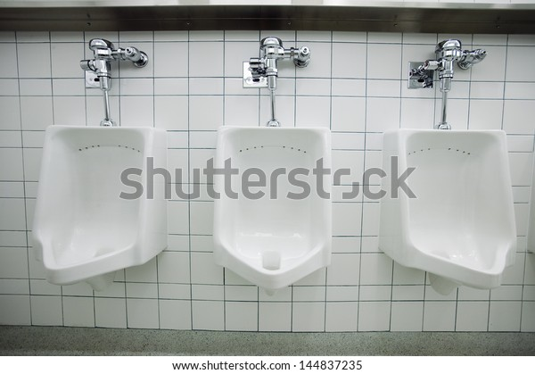 Closeup of three white urinals in men's bathroom
