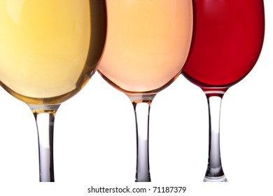 Close-up of three wineglasses. Yellow, pink and red