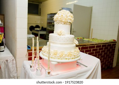 A closeup of a three-floor wedding cake decorated with flowers on the table in the kitchen