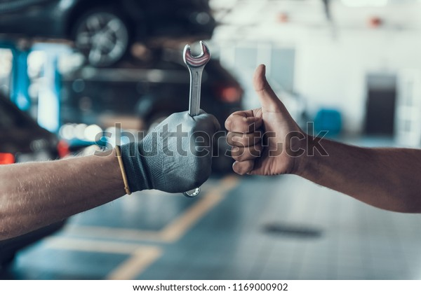 Close-up Thumb Up and Mechanics Hand with Tool. Automobile Master Wearing Gloves Showing Positive Gesture after Finishing Work. Technic occupation. Automobile Repair Service Concept.