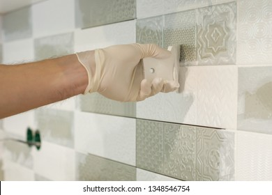 Closeup of tiler hand rubbing tile, Installing and grouting decorative finishes in environments with an high aesthetic value. Two-component, decorative, acid resistant epoxy grout.