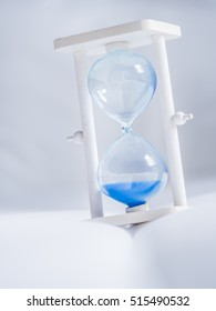 Closeup of time out hourglass on white fabric texture