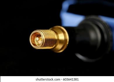 Closeup of a tire valve and a fragment of TPMS sensor housing.