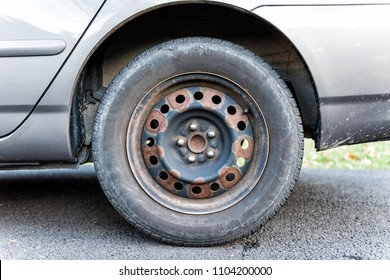 Closeup of tire wheel with missing cap cover on parked car, rust, hubcap