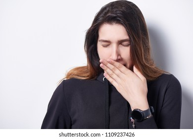 Closeup of tired woman yawning covering a mouth with her hand