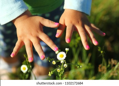 Closeup of toddler girl's nails painted pink