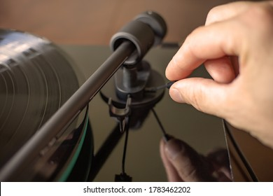 A close-up of the tonearm of a black turntable. The hand raises the tonearm.