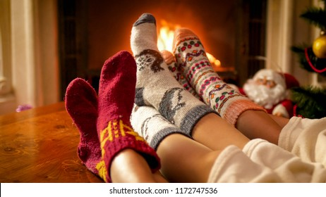 Closeup toned photo of family in knitted socks warming by the fireside on Christmas eve