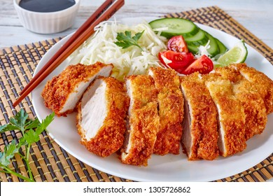 close-up of Tonkatsu - panko breaded deep-fried pork cutlet served with fresh shredded cabbage salad, tomatoes and lime slices on a plate on a bamboo mat, Japanese cuisine, view from above
