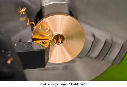 Close-up of a tool bit when turning on a lathe. Bronze product clamped in a rotating chuck of the machine in background. Twisted swarf and mirroring a triangular cutter on the golden workpiece.