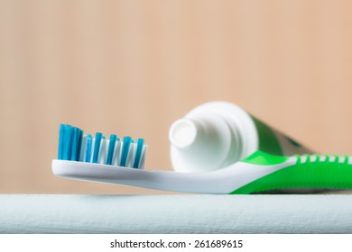 Close-up of a toothbrush and tube of toothpaste on the edge of a bathroom counter from a low angle view.