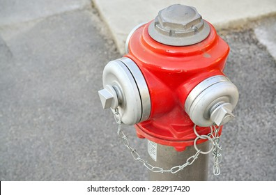 Closeup of the top part of a red fire hydrant on the sidewalk