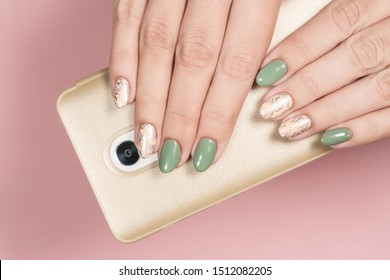 Closeup top view of beautiful manicured female hands holding modern mobile phone isolated on pastel pink background. Fingernails with colorful  trendy gel polished design with silver stamping on beige