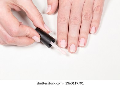 Closeup top view of brush with pink gel polish and painted manicured female hands isolated on white table background. Horizontal color photography.