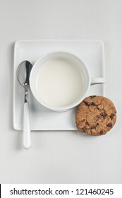 Closeup top view of cup with milk, spoon and chocolate cookie on plate on white wooden background.