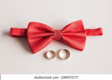 Closeup top view of elegant stylish red male bowtie and two golden rings isolated. Preparation for wedding day concept. Horizontal color photography.