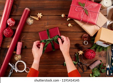 Close-up top view of female hands decorating red gift boxes with backer s twine and fir brunches on wooden table. Pine cones and christmas decoration on dark desk.