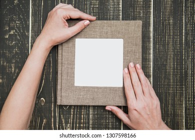 Closeup top view of female hands holding brown canvas photo book with empty white space in middle for text or photography. Album isolated on brown wooden background. Horizontal image with copyspace.