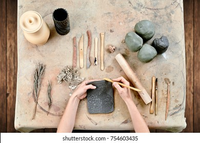 Close-up top view of a female potter  makes out of a bricks-like clay large flat plate on a wooden table in a workshop. female potter molding clay with rolling pin in pottery workshop