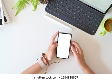 Closeup and top view of female using mobile smartphone on office white desk