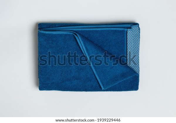 Close-up top view of folded blue towel on gray background.