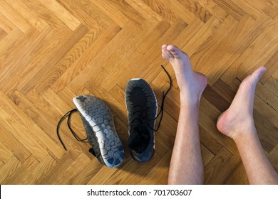Closeup top view image of barefooted male athlete's crossed legs aside black sport shoes and socks on wooden floor background. That was quite a run. Copy space