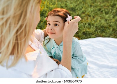 Closeup top view image of happy child looking to her mother in the park. Beautiful young woman and her daughter spending time together. Mom and little girl shares love. Happy Mothers Day. Childhood