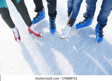 Closeup top view of legs in modern skates on ice rink.  Friends skating together outdoors  at winter frozen lake