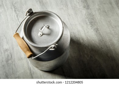 closeup top view of old kind of aluminum bidon with wooden handle for milk storage on gray background