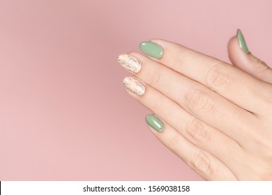 Closeup top view of one beautiful perfect manicured female hand isolated on pink pastel background. Fingernails with trendy two colors naildesign decorated with silver stamping on beige nails.