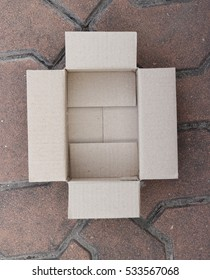 Close-up top view of an open empty cardboard box on marble background.