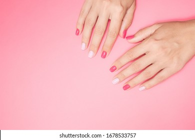 Closeup top view photography of two beautiful female hands isolated on pastel pink background with empty space for text. Fingernails with modern trendy assymetric two colors design of manicure.