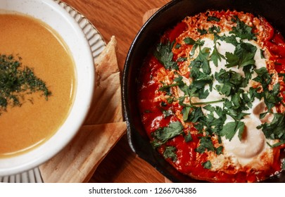 Closeup Top View Of Pumpkin soup and shakshouka scrambled eggs with paisley served on pan middle eastern breakfast