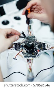 Closeup top view shot of male hands unscrewing circuit board of disassembled drone on white table with assorted tools